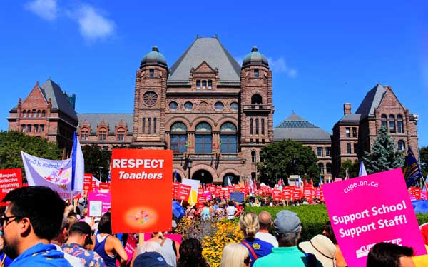 Teachers rally at Queens Park on Aug. 28 against legislation that would take away their right to collective bargaining for two years. Photo: Preeteesh Peetabh Singh / the Dialog