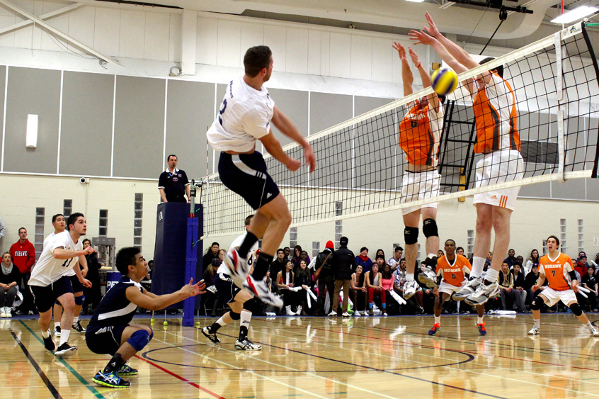 Mohawk players block a shot by the Huskies men's volleyball team during a playoff match on Feb. 16. Photo: Preeteesh Peetabh Singh / The Dialog