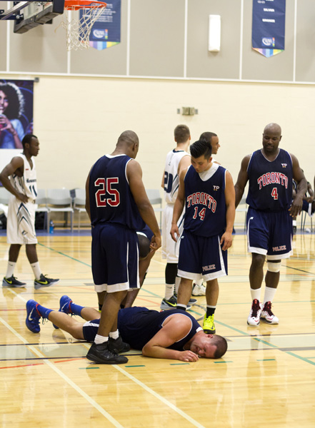 A Toronto police officer lays injured on the court during  an exhibition basketball game on Friday. The Huskies basketball team beat the Toronto Police's squad 90-56.  Photo: Preeteesh Peetabh Singh/The Dialog
