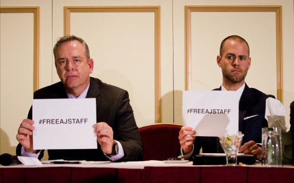 Owen Watson, executive producer for news at Al Jazeera English & Tom Henheffer, executive director of Canadian Journalists for Free Expression hold up #FreeAJStaff signs at a press conference in Toronto on Feb. 6. Photo: Preeteesh Peetabh Singh/The Dialog