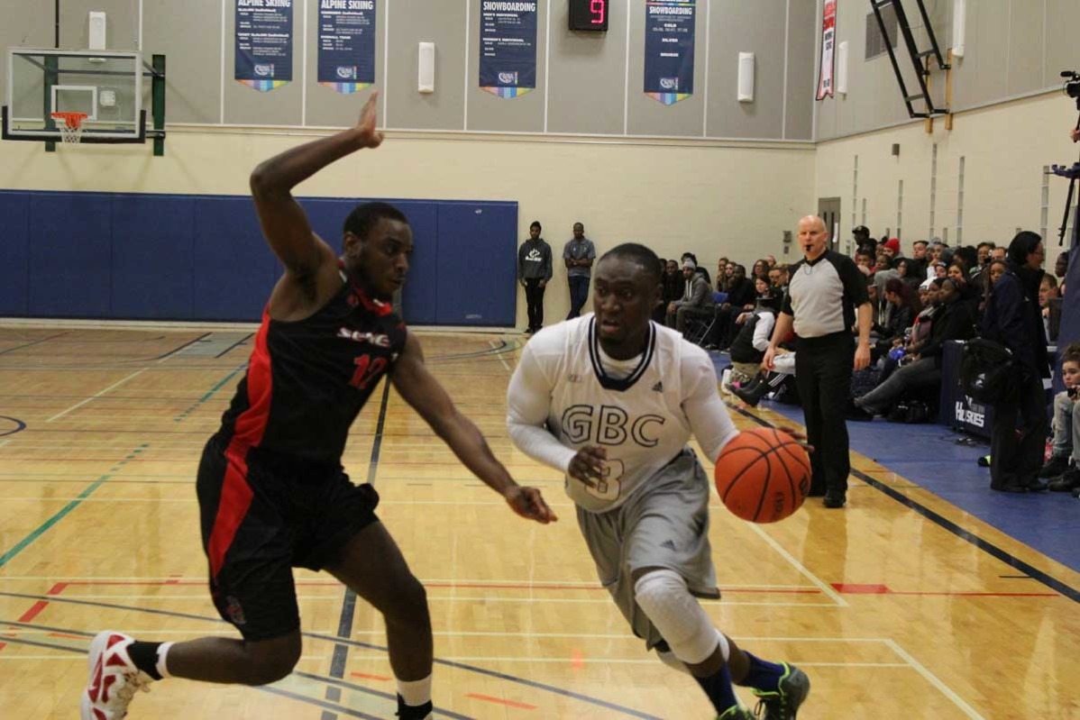 Curtis Baanee, right, of George Brown College dribbles past Adrian Tucker of the Seneca Sting in the Huskies' home opener on Oct. 22. Photo: Brittany Barber/The Dialog