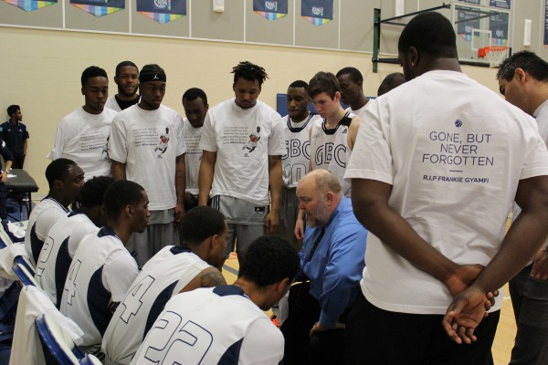"Head coach Jonathan Smith huddles with Huskies men's basketball players wearing memorial shirts reading ""Gone but never forgotten. RIP Frankie Gyamfi"" on the Nov. 21 ""night to remember"" basketball game. Photo: Brittany Barber/The Dialog"