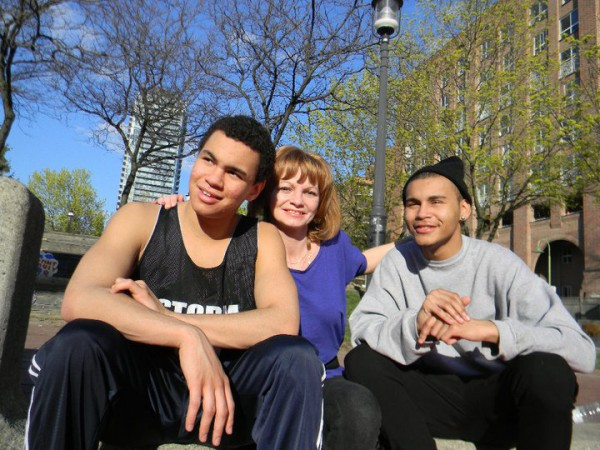 Deborah Crane, centre, sits with her son Kurtis Crane (left) and nephew Dexter Stewart (right) at the basketball court they helped renovate as part of the Esplanade Youth Movement.
