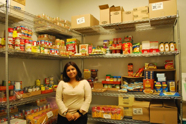 Lamees Rahim standing at the Food Bank with supplies in the stocked shelves in the background