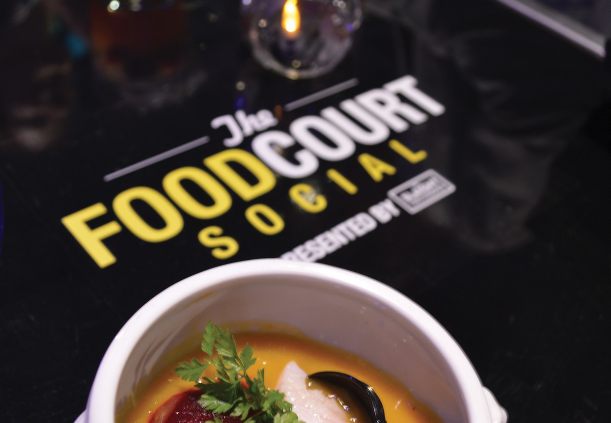 Image with Gourmet Food in a bowl and drinks with a candle light on table mat labeled The Food Court social in background.