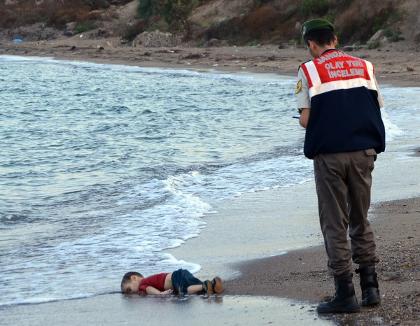 FILE - In this Sept. 2, 2015 file photo, a paramilitary police officer investigates the scene before carrying the lifeless body of Aylan Kurdi, 3, after a number of migrants died and others were reported missing when boats carrying them to the Greek island of Kos capsized near the Turkish resort of Bodrum. The tides also washed up the bodies of the boy's 5-year-old brother Ghalib and their mother Rehan on Turkey's Bodrum peninsula. Their father, Abdullah, survived the tragedy. (AP Photo/DHA, File)