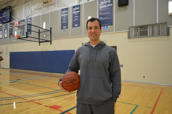 Image of the Huskies women's varsity basketball coach Mr. Fatih Akser standing in the basketball court with a basketball in his hand
