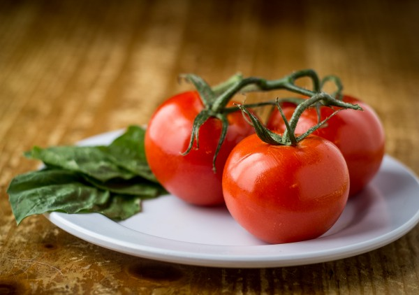 Image of Tomatoes and Basil in a platter on awooden table