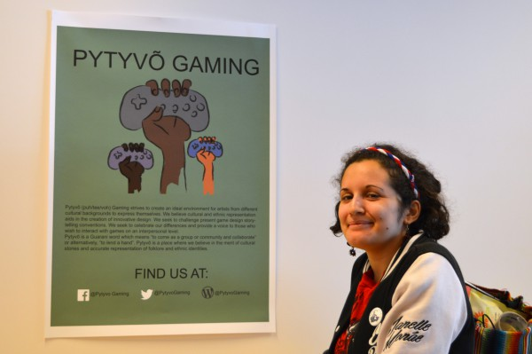 Image of a poster on wall with text Pytvo Gaming with image of brain in a fist and the founder Gabriela Aveiro standing next to the wall