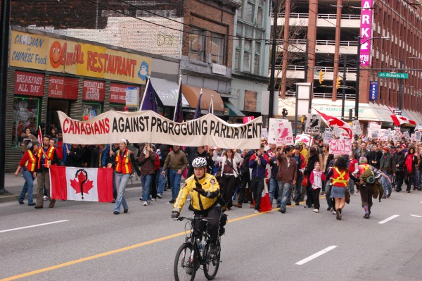 Image of Canadians marching with flags against Proroguing Parliament.at a Vancouver Rally