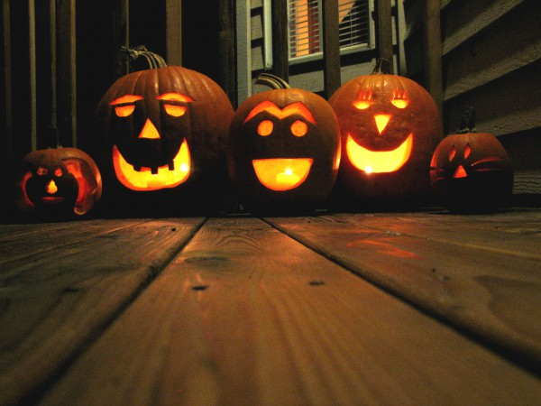 Image of 5 halloween candle lit pumpkins on a wooden floor
