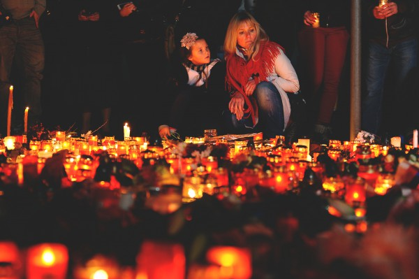 Image of a woman and a girl sitting beside lit candles
