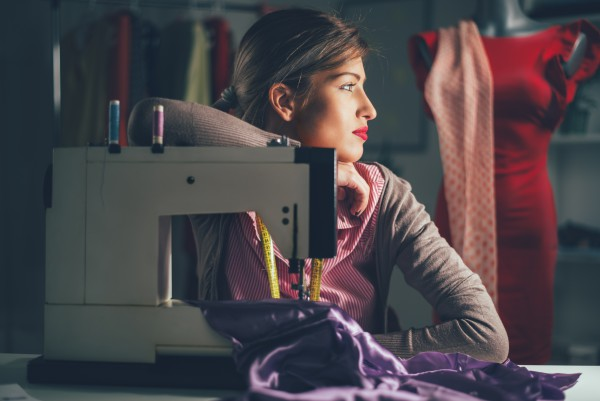 Image of Beautiful tired woman sits in front of the sewing machine and thinking. Vintage fashion concept.
