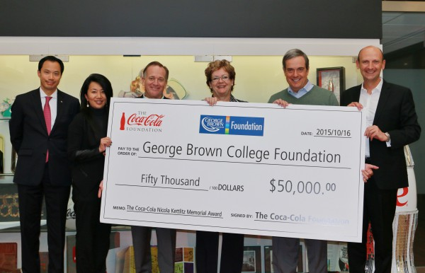 Image of Coca-Cola Foundation donating a large cheque of 50000 dollars to George Brown College members standing behind it