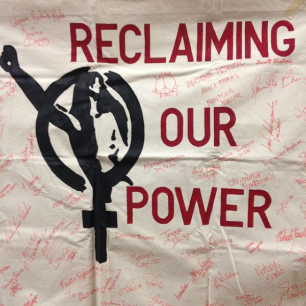 "Banner of a women's symbol with a woman raising a fist and the text ""reclaiming our power""."