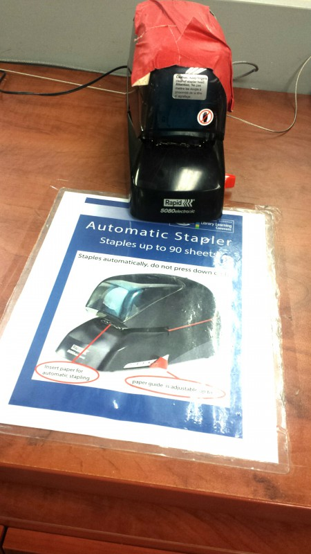 Photo of automatic stapler with red duct tape.