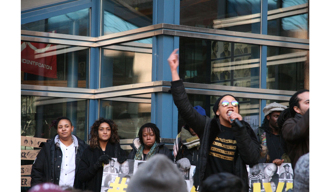 Photo of a woman with her arm in the air holding a microphone speaking to a Black Lives Matter Toronto rally on March 26