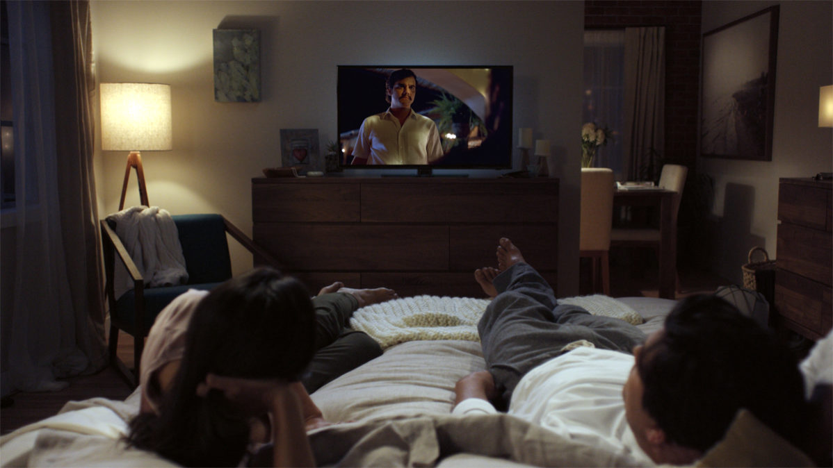 Photo of two poeple on a bed wathing a TV courtesy of Netflix