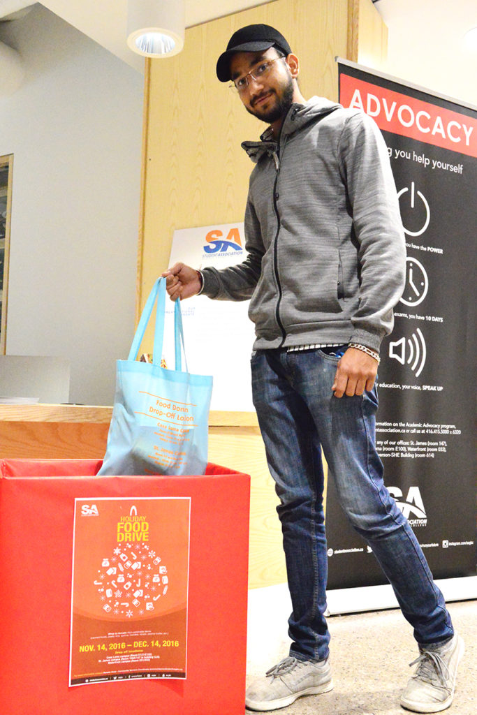 Taranpreet Singh, support staff at the SA food bank drops off some non-perishables in the food drive box Casa Loma. Steve Cornwell / The Dialog