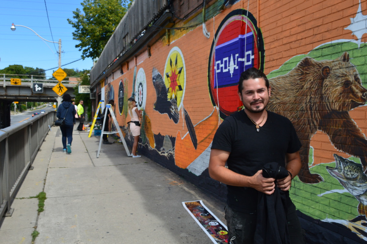 Cesar Rodriguez helped paint the new Indigenous themed mural at Spadina and Dupont. Photo: Megan Kinch / The Dialog