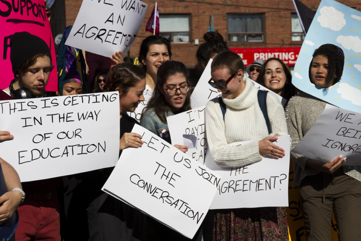 "Students look at their chant sheet and hold their signs at Humber College's Lakeshore Campus on Friday, October 20, 2017. The chant included lines like ""We're mad at the college, not at our teachers"" and ""This is not fair, just get it together."" Photo: Kit Kolbegger / The Spare"