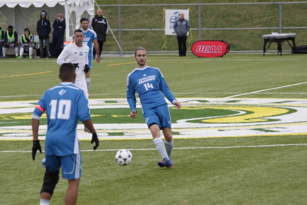 Justin Soscia (14) controls the ball as Jesse Oliver looks on against Niagara. Photo: OCAA