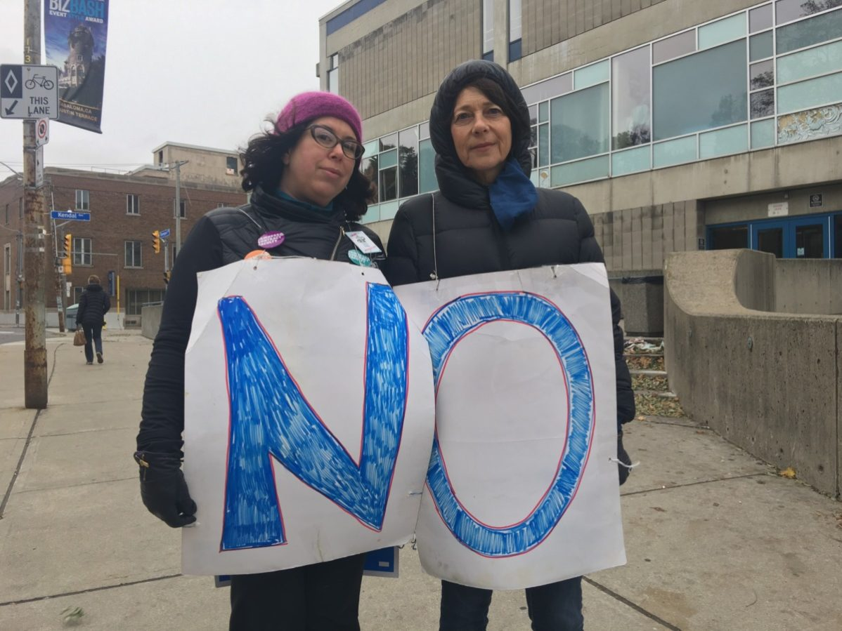 "Two picketers at George Brown College's Casa Loma campus wear signs spelling ""no"" on the morning that striking college faculty rejected an offer fro the colleges by 86 per cent. Photo: Lidianny Botto / The Dialog"