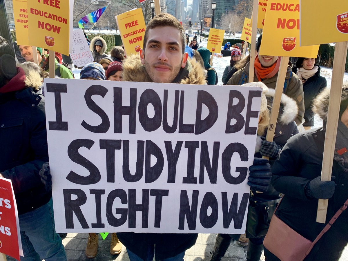 A student holds a home-made sign at the protest at Queen's Park on Feb 19. Photo: Kevin Goodger / The Dialog